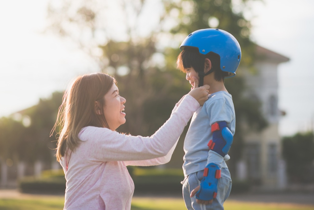 Mom helping her son put on a helmet.