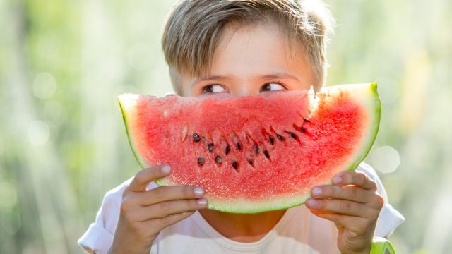 kid holding a watermelon in front of his face as if it is a smile, things you should never lie to kids about