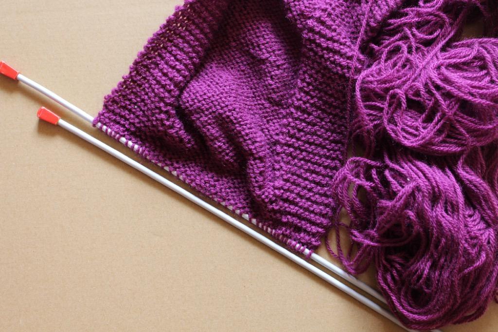 knitting needles and purple yarn