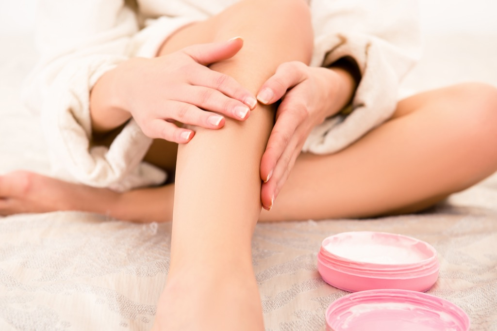 Woman putting lotion on her legs.