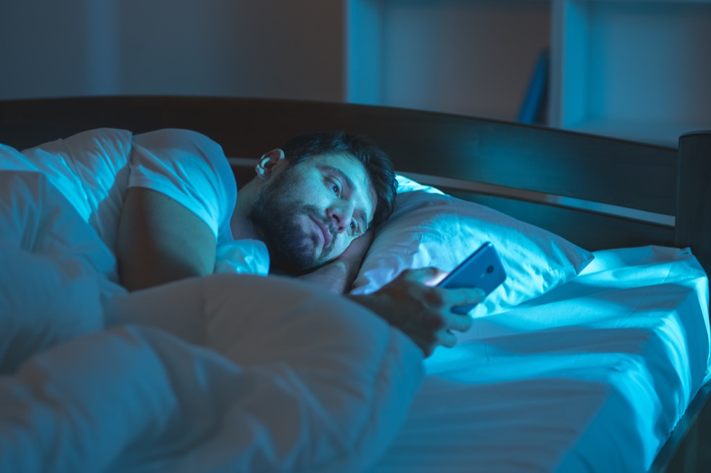 Man is alone in bed reading his phone perfect nap