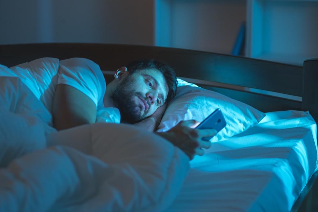 Man is alone in bed reading his phone health tweaks over 40