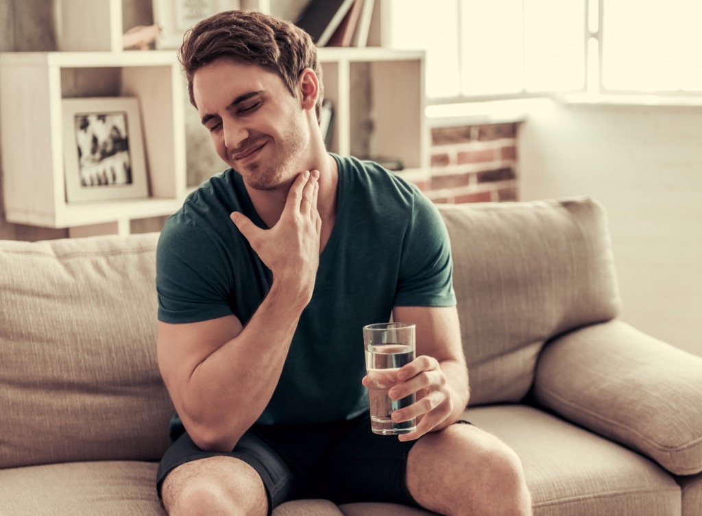 man holding a glass of water sitting on a couch