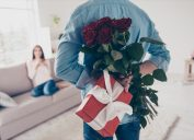 white man holding roses and a gift behind his back