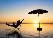 man relaxing on beach at sunset in a chair - funniest jokes