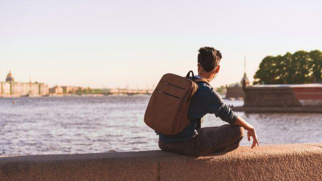 man sitting alone by a european river