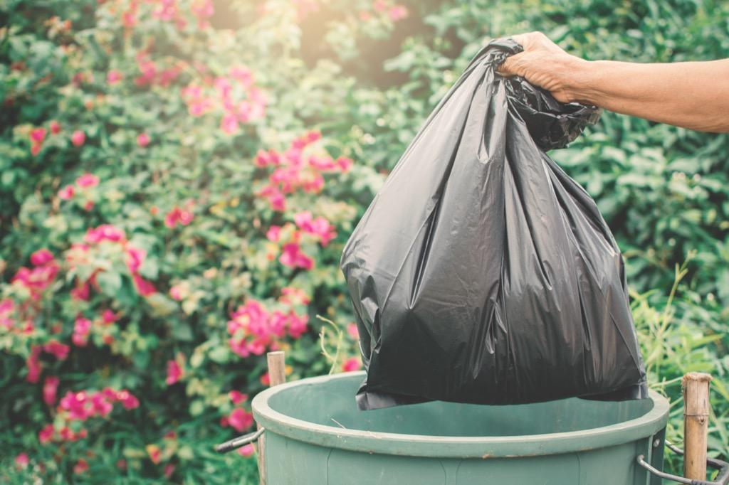 man throwing garbage in trash can