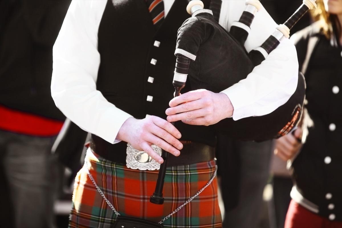 man playing bagpipes wearing a kilt