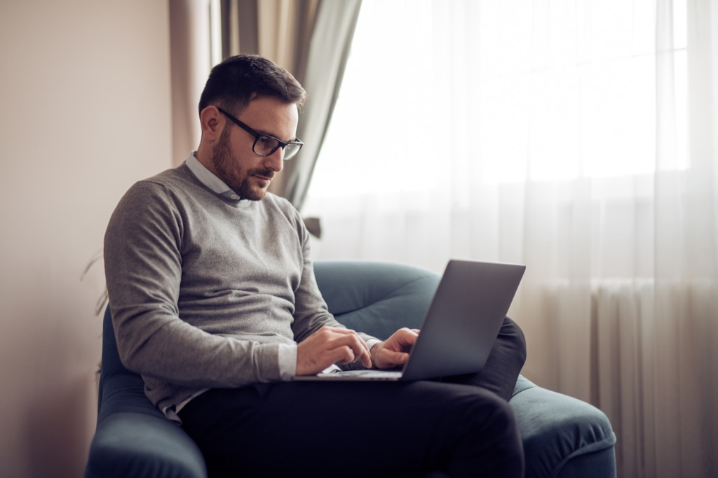 man sitting with laptop on lap, healthy sex after 40