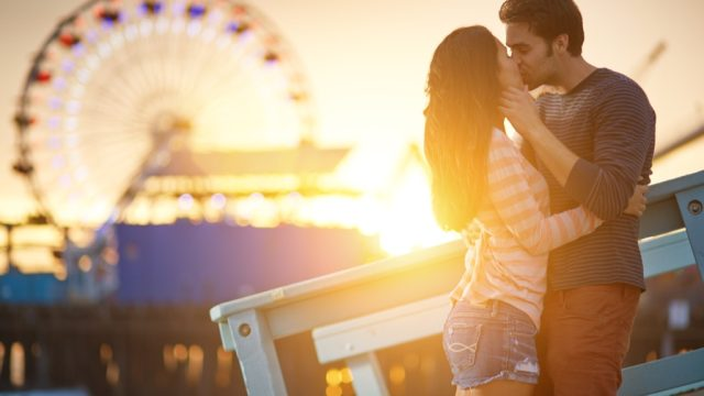 a man and woman kissing in front a ferris wheel