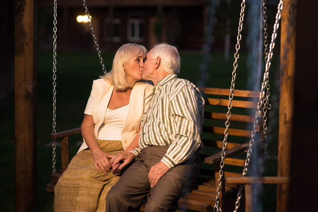 old couple kissing on a porch swing