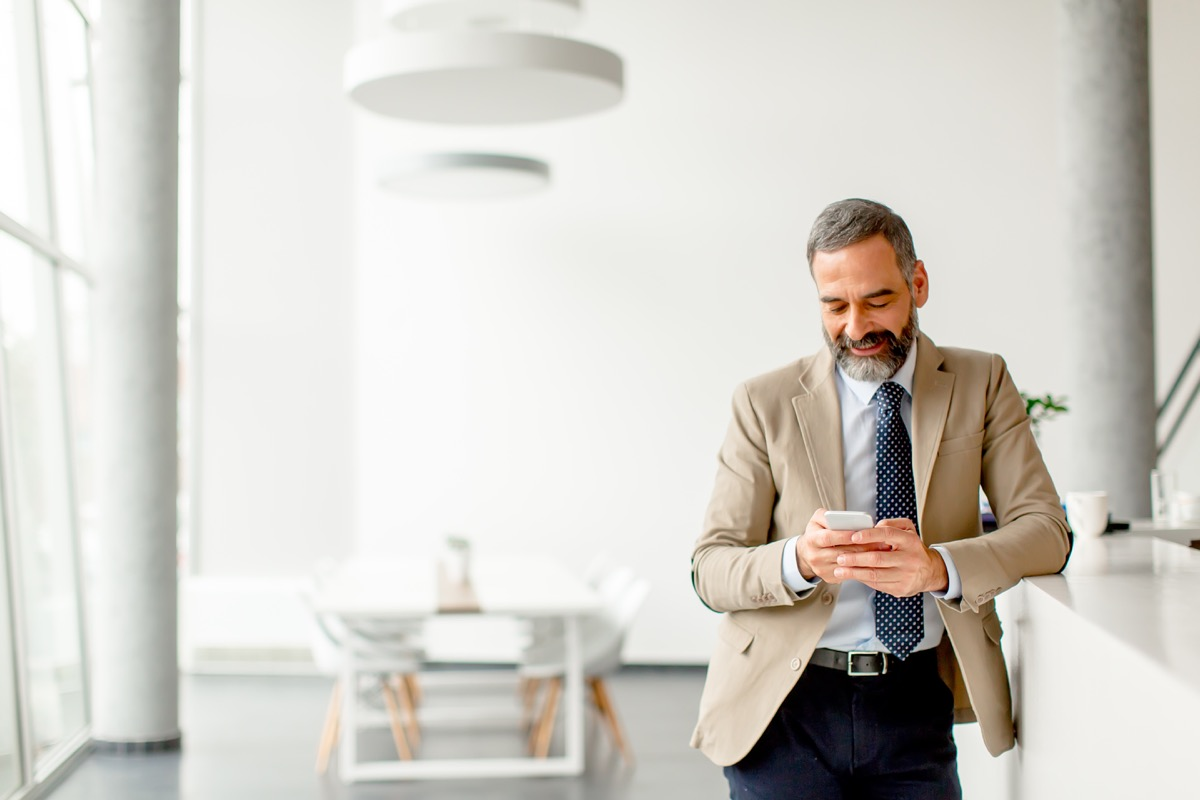 older man sending an email on phone, smart person habits