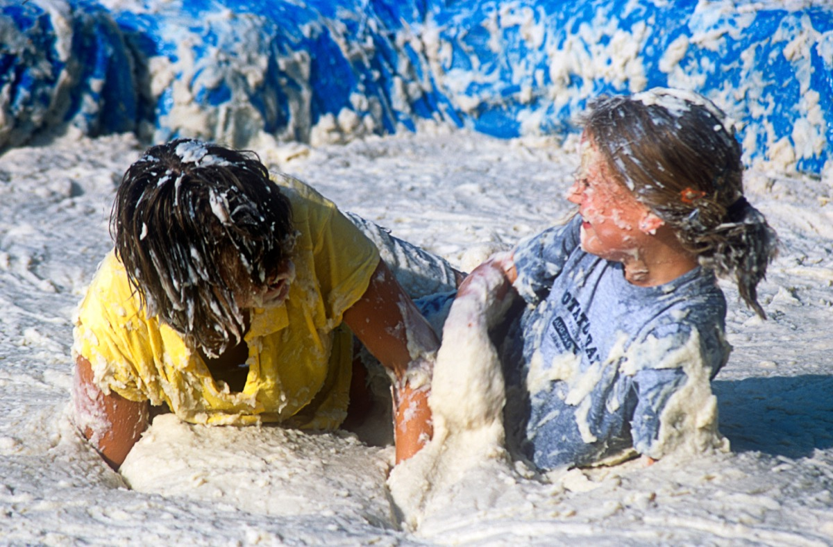 people competing in a mashed potato wrestling contest