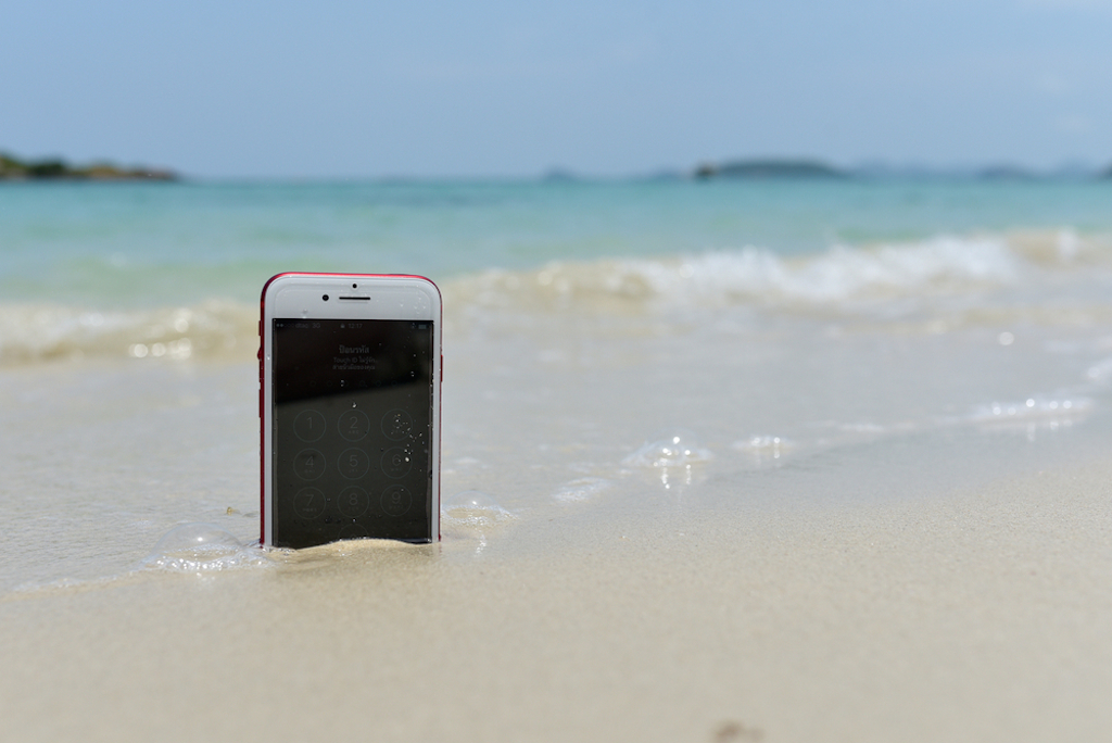 phone in sand and water at beach
