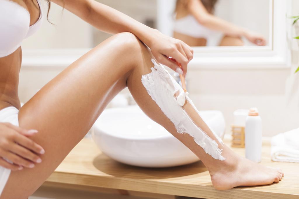 close-up of woman shaving legs