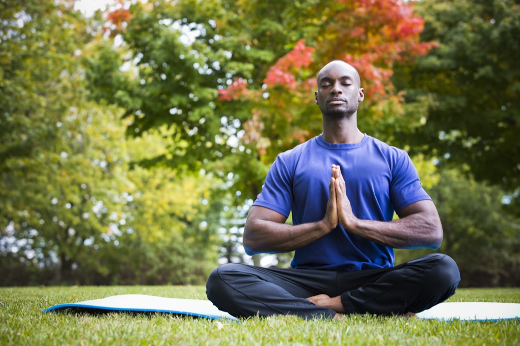 man meditating in the lawn, ways to feel amazing