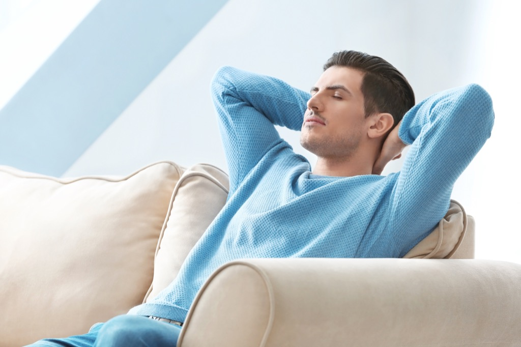 man in blue sweater relaxing on couch