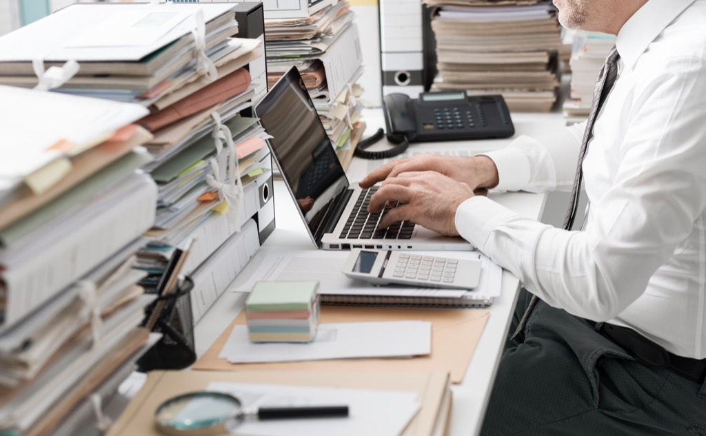 Frustrated businessman at the computer with stacks of paper.