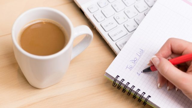 Woman being productive and writing a to-do list, ways to feel amazing