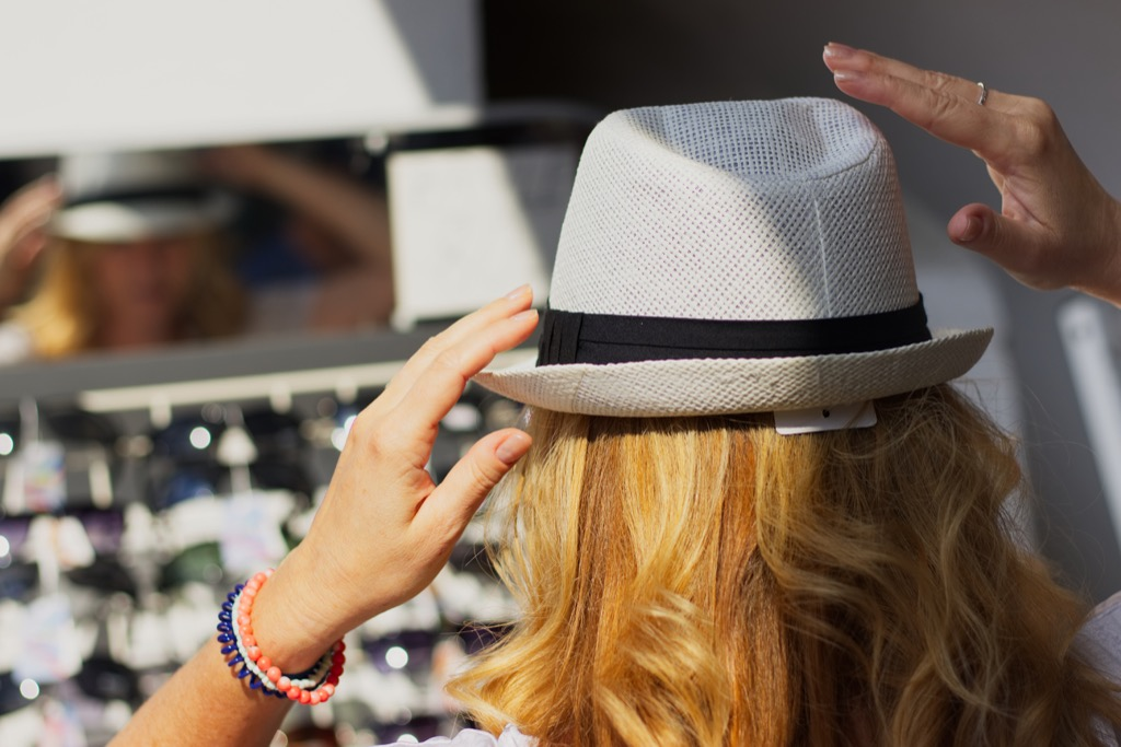 Woman trying on a hat at the market.