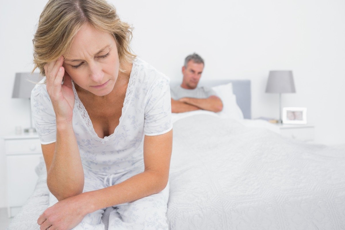 older woman looking upset in bed while man sits behind her