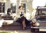 1950s-style woman sitting next to car