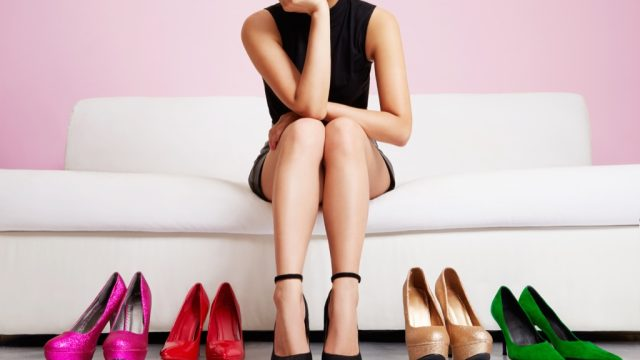 woman choosing shoes while on a sofa in a room with pink walls