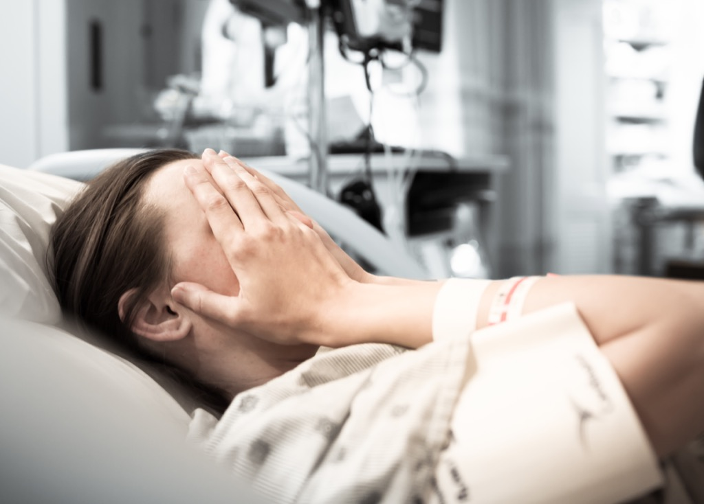 Woman crying in a hospital bed.