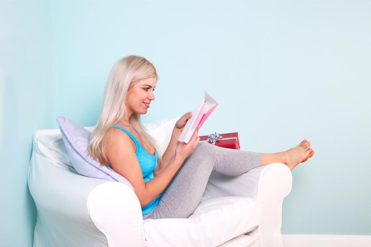 woman in an armchair reading a birthday card