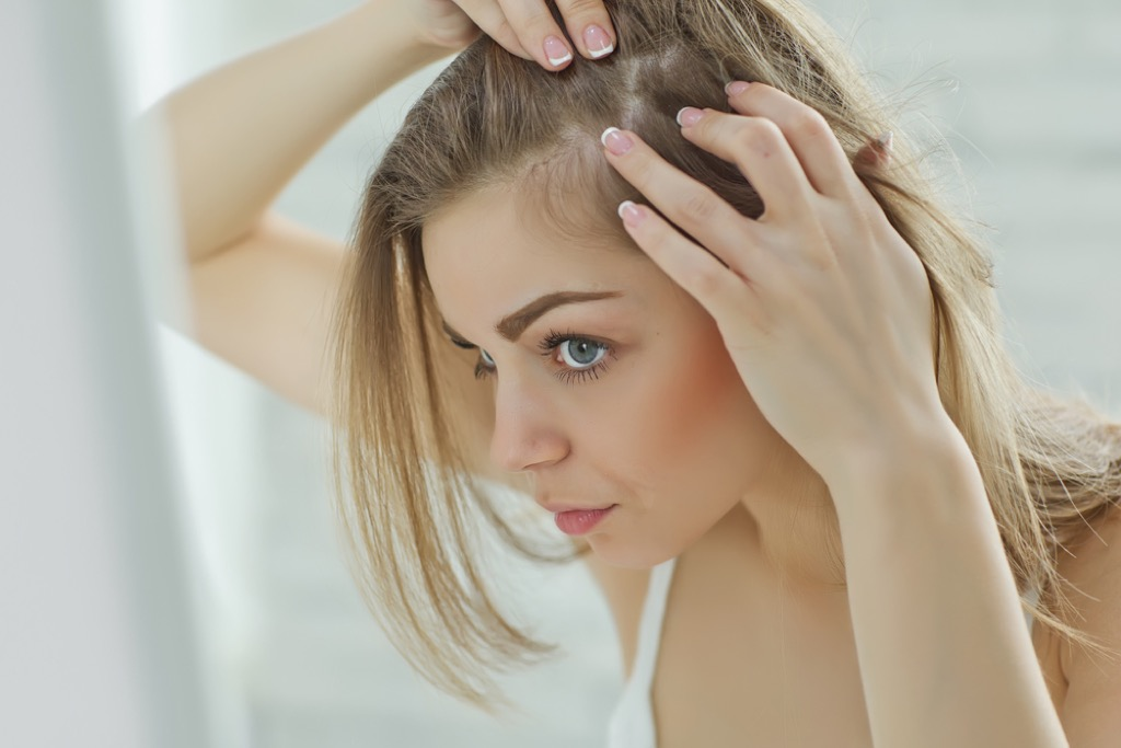 Woman Looking at Scalp Signs Your Hair Will Go Gray