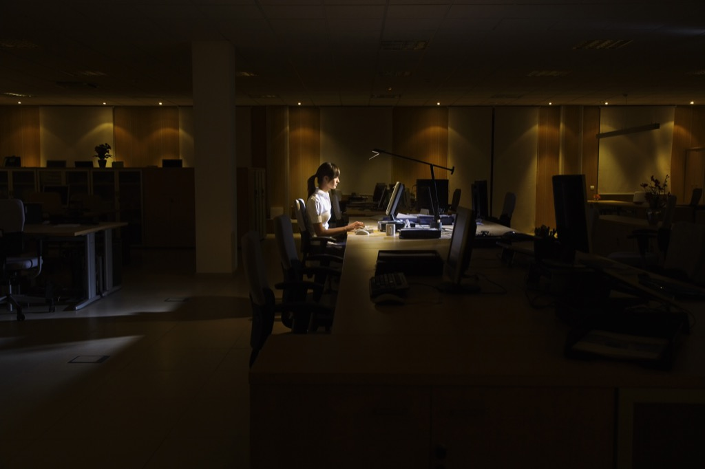 Woman is working hard at night, last one in the office.