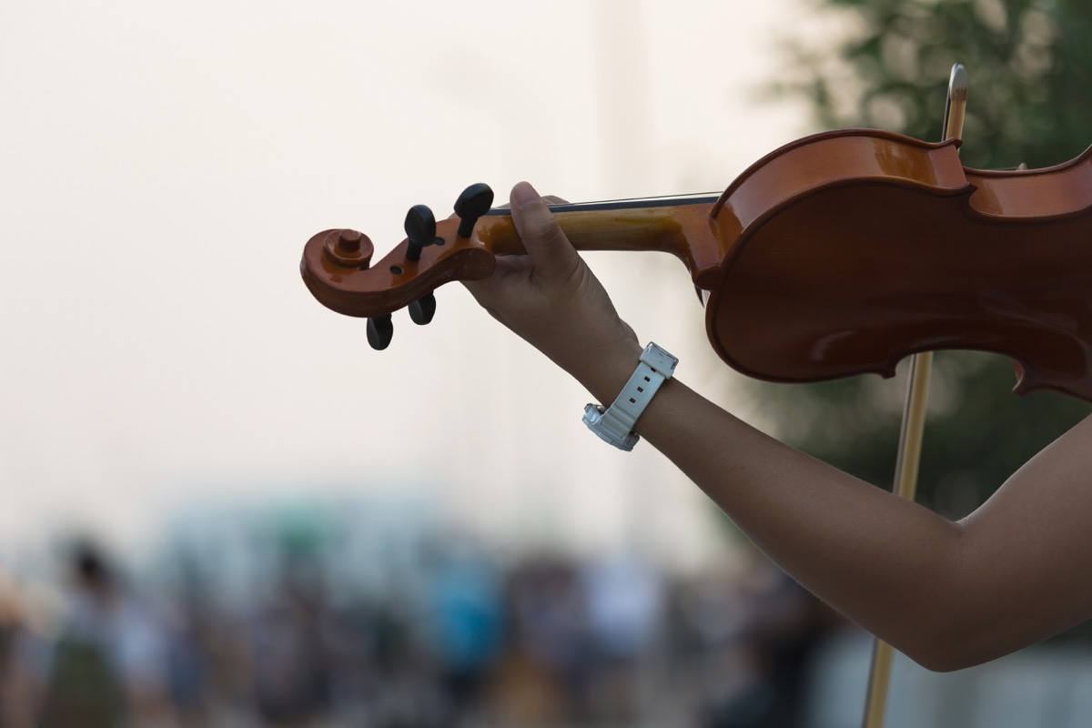woman playing a fiddle in front of a large audience