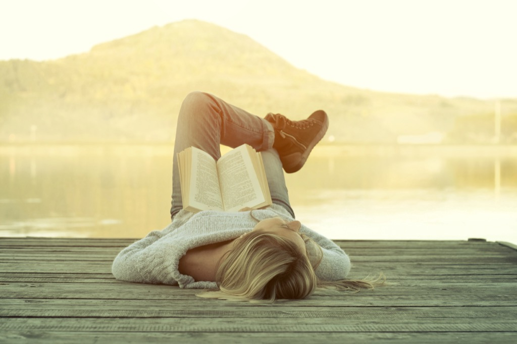 woman relaxing on a dock at sunrise with a book