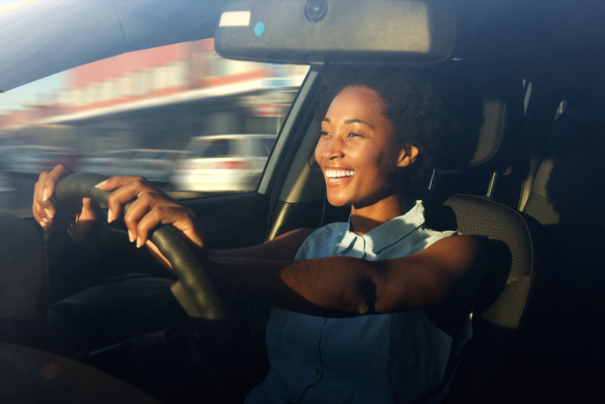 woman smiling while driving in the car