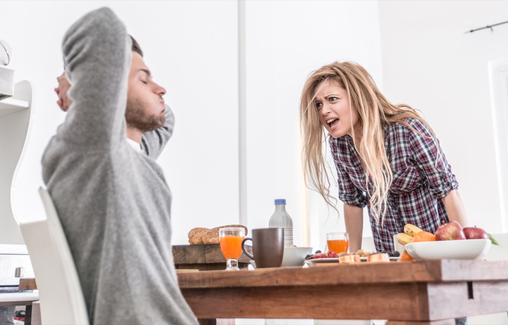 Woman yelling at her boyfriend in the kitchen, signs of cheating