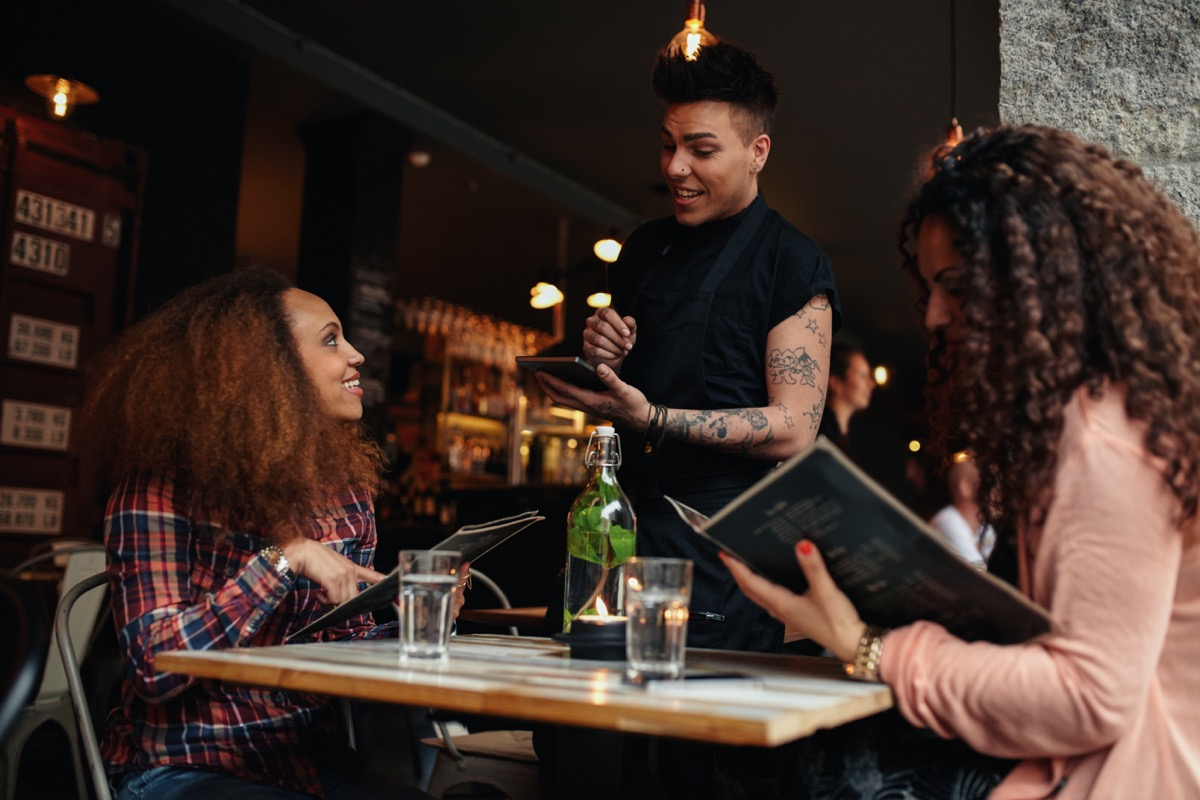 women ordering food from a waiter in a restaurant