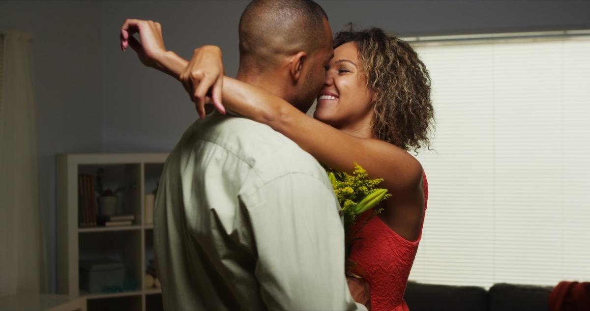 30-something black man giving girlfriend flowers