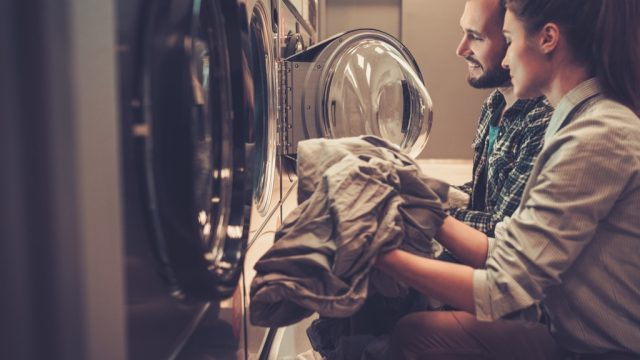 young couple doing laundry in a laundromat
