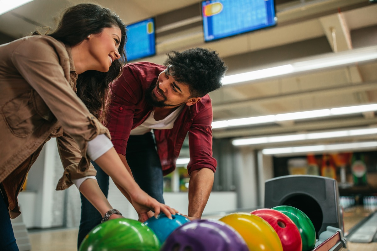 young interracial couple bowling together