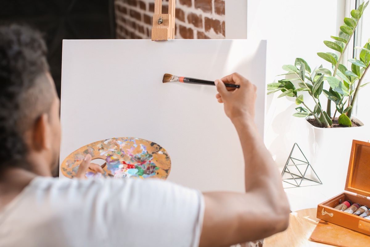African-American man painting on canvas