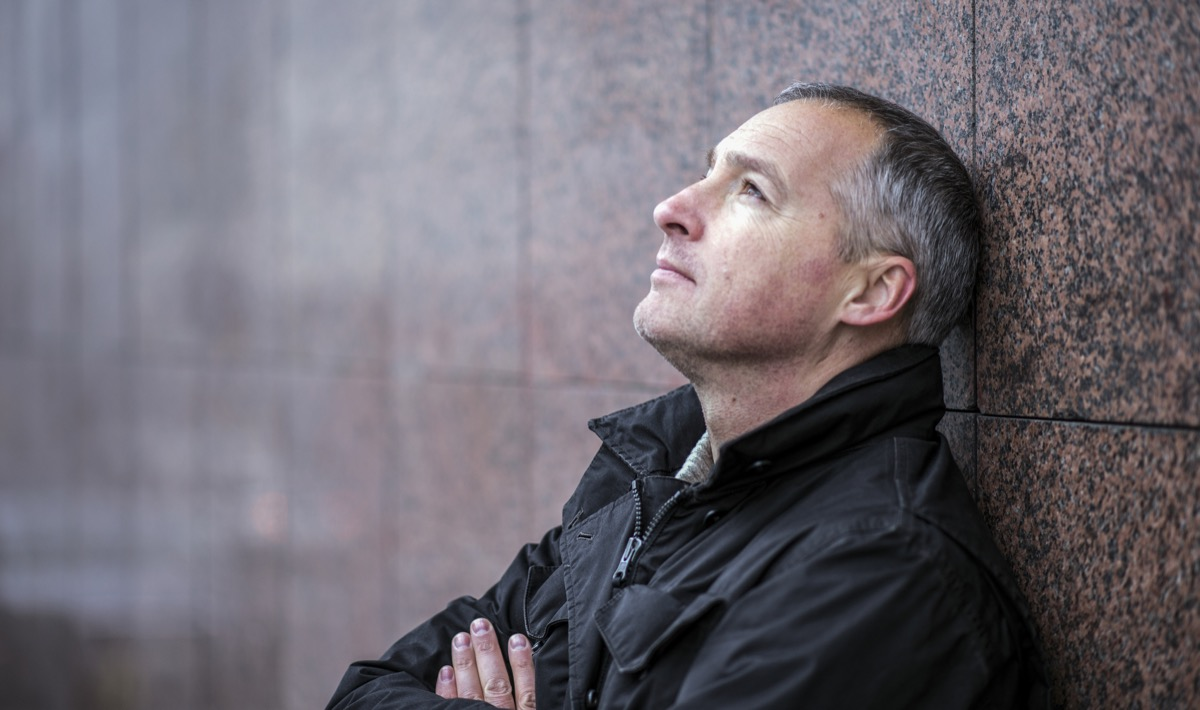 Mature man lost in thought standing outside and looking up