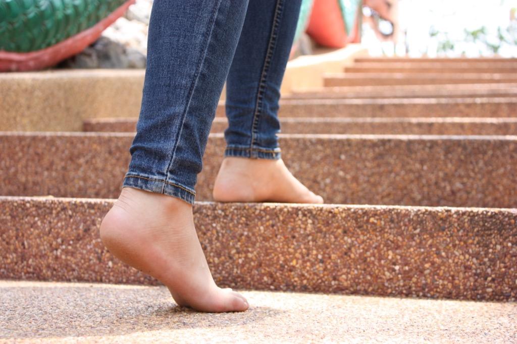 Woman walking barefoot up stairs