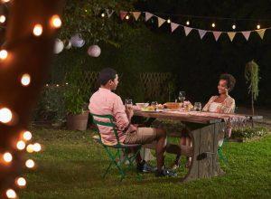 young black couple having dinner outside in garden