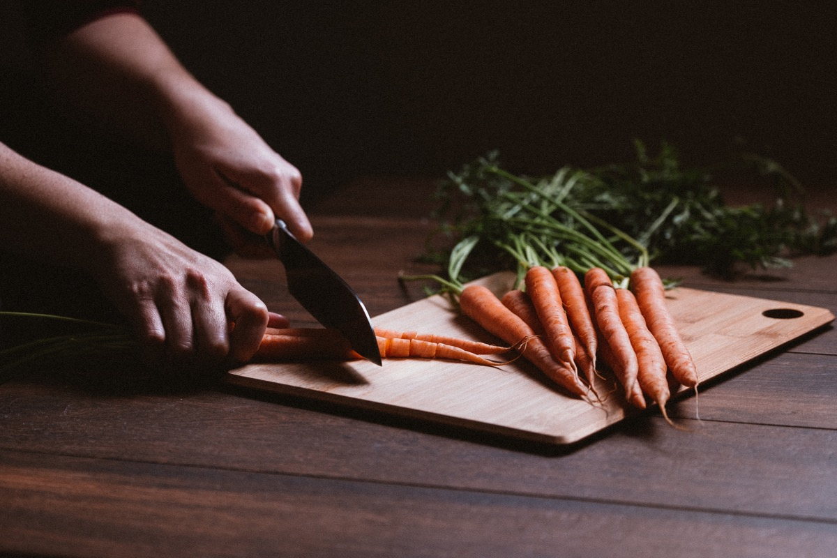 A bunch of fresh raw carrots with stemsWoman cutting carrots and a bunch of fresh raw carrots with stems