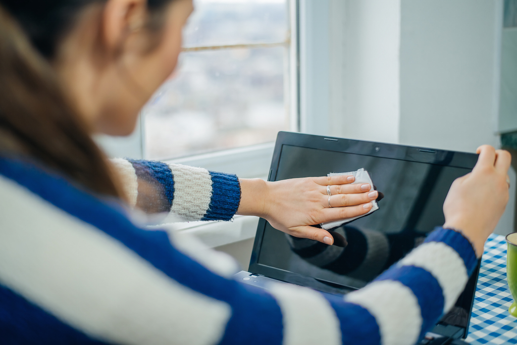 Woman is cleaning her computer screen with a cloth.