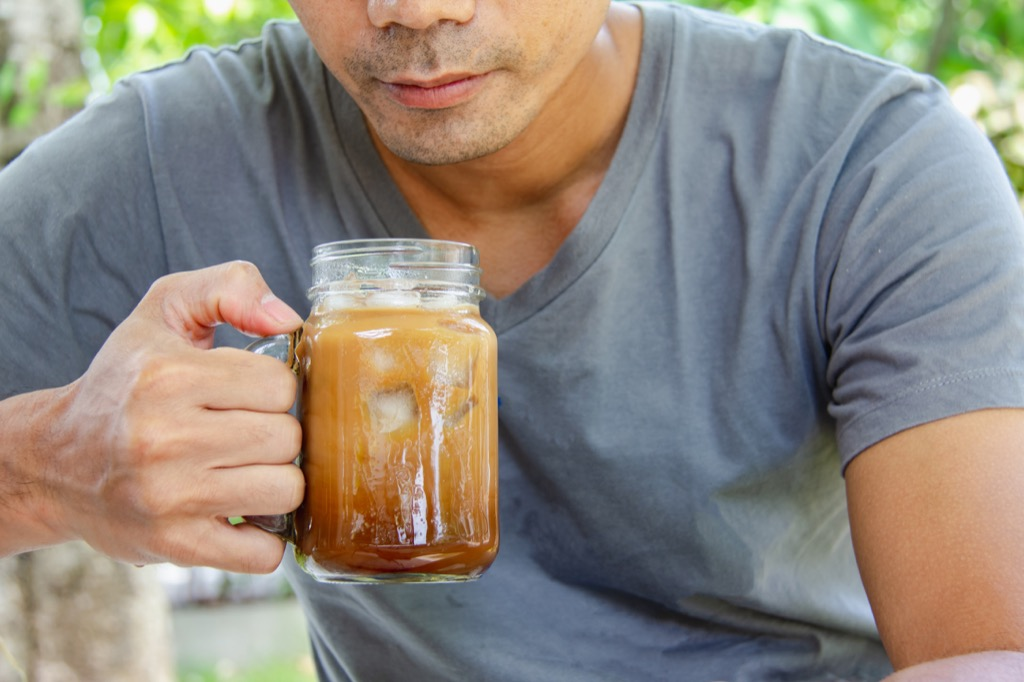 Man drinking iced coffee without a straw, best anti-aging tips