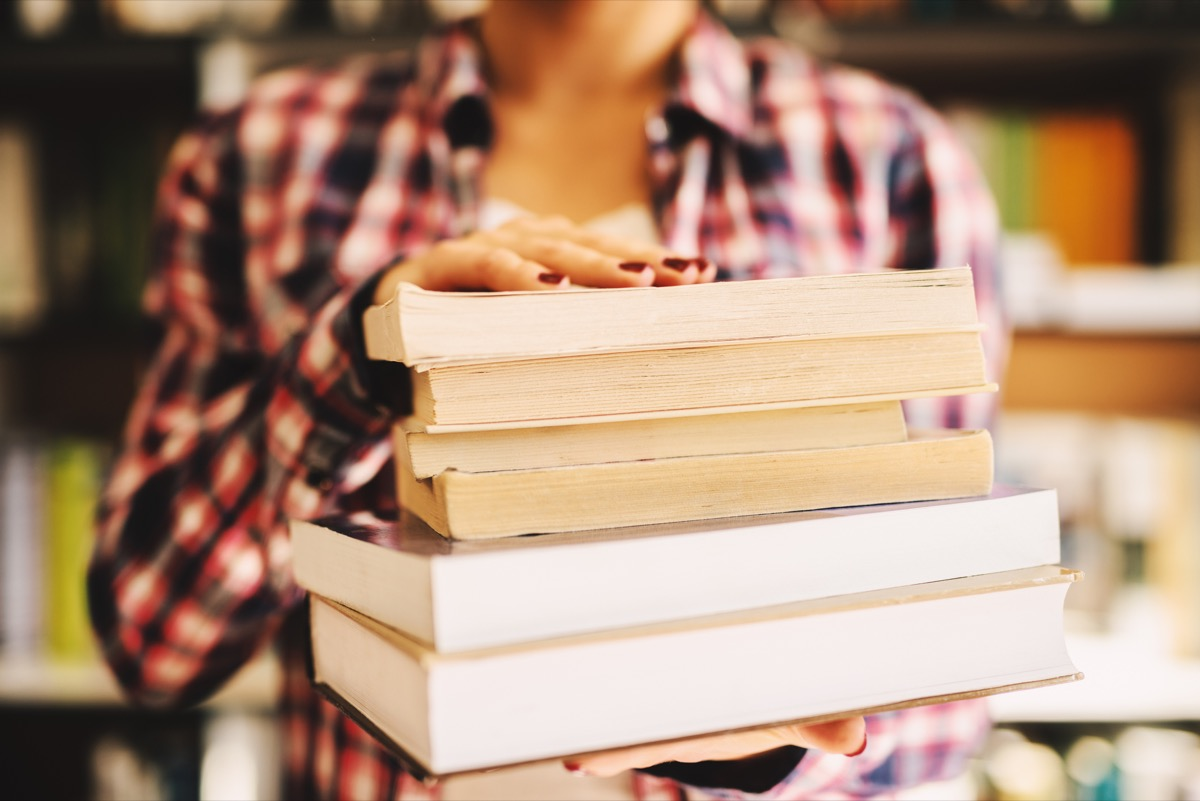 Close up of woman holding stack of books