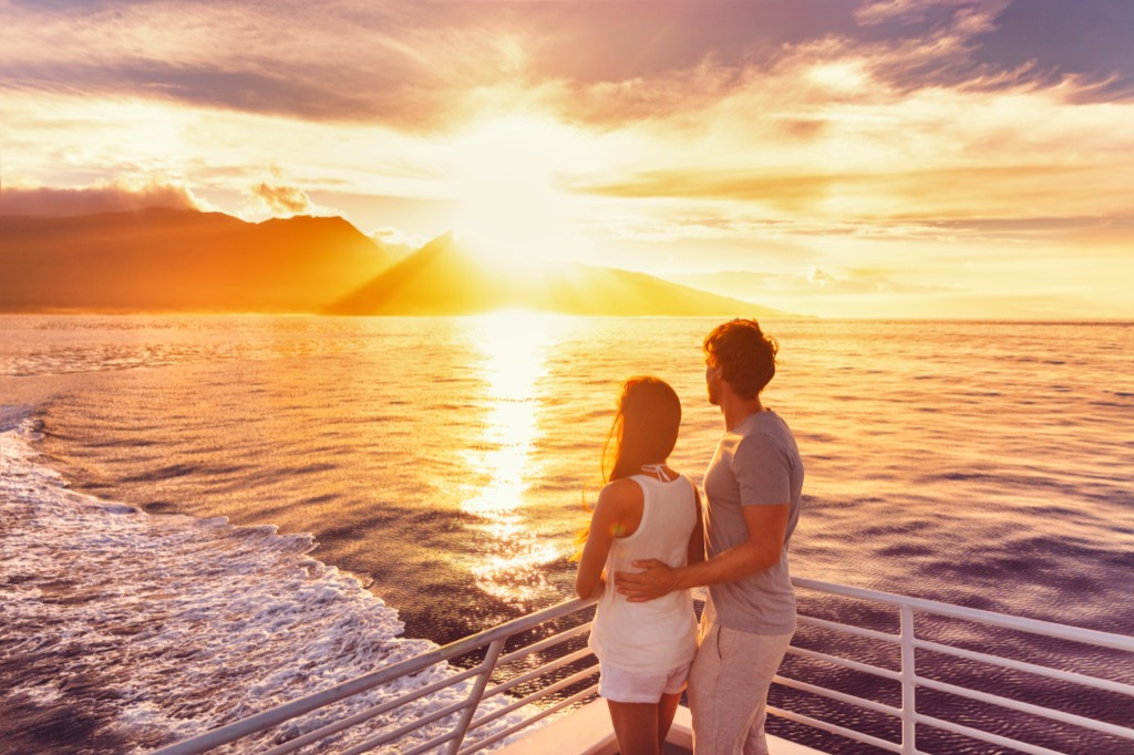 Couple on a cruise looking out at the sunset