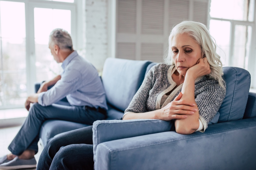 Older couple having an argument and fighting on the couch, over 50 regrets