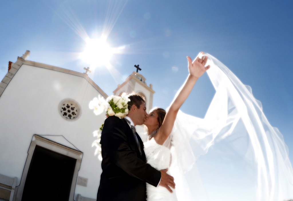 couple kissing outside church 20 Old-Fashioned Wedding Traditions That Nobody Does Anymore